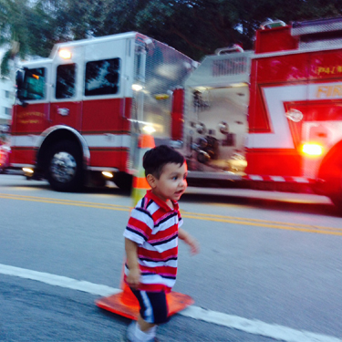Toddler in front of a fire truck
